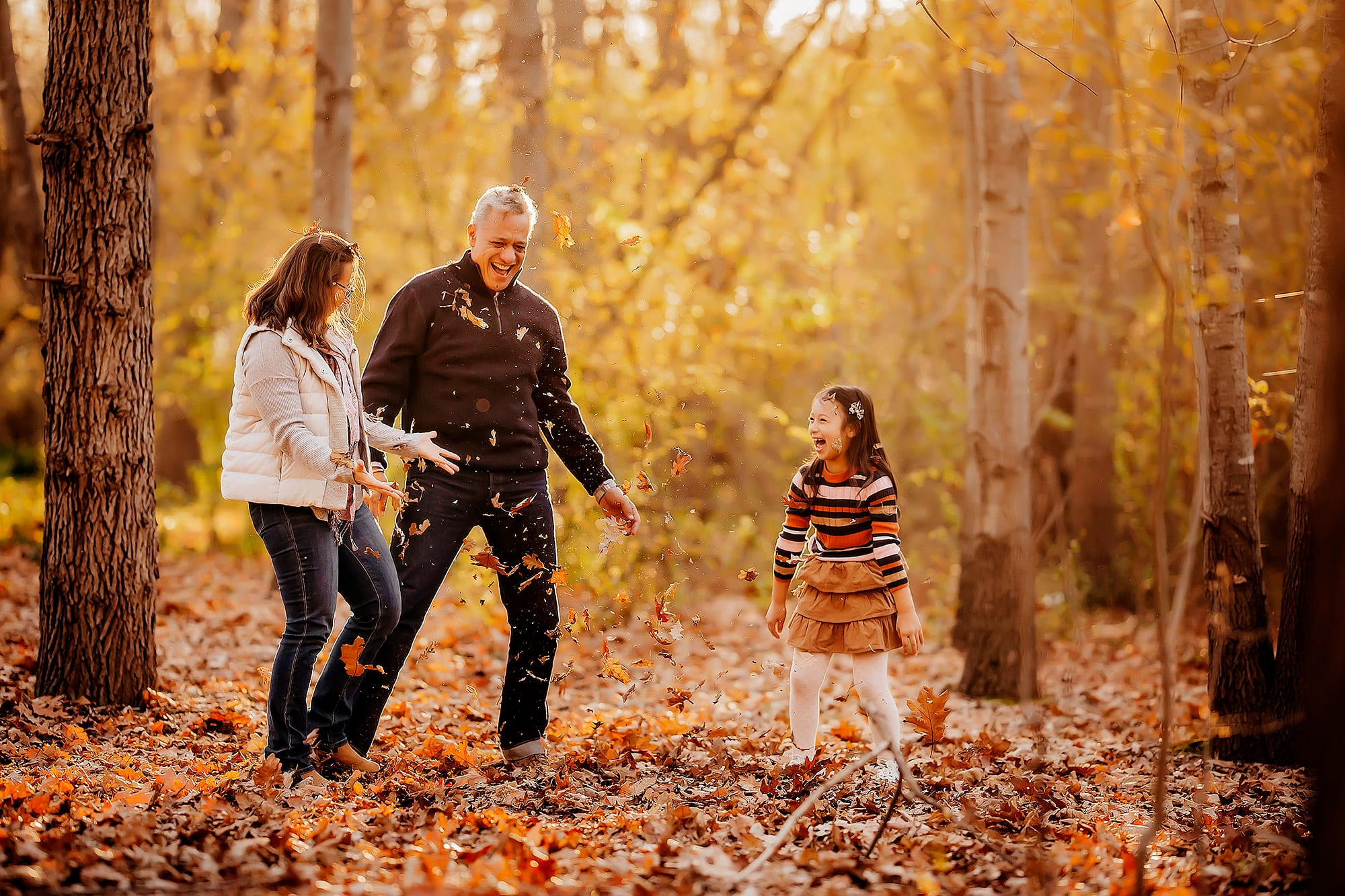 Family playing in autumn leaves